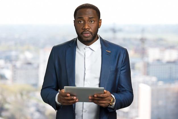 Удивленный бизнесмен с планшетом компьютера. грустный черный менеджер держит цифровой планшет