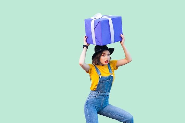 Удивленная забавная молодая девушка в хипстерской одежде в джинсовом комбинезоне и черной шляпе стоит и держит под головой гигантскую большую тяжелую подарочную коробку с невероятным лицом. студия выстрел, зеленый фон, изолированные