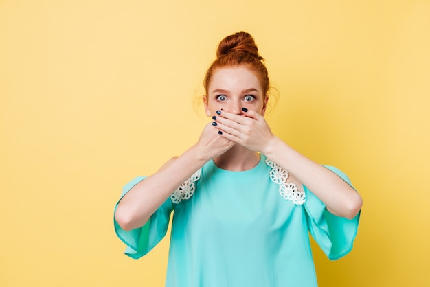 Suprised ginger woman covering her mouth and looking