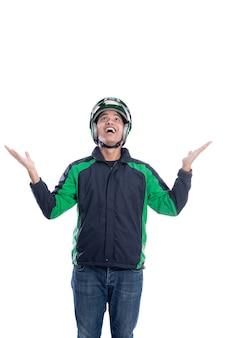 スペースをコピーするために見上げるヘルメットを持つ驚いた男性のオートバイのライダー