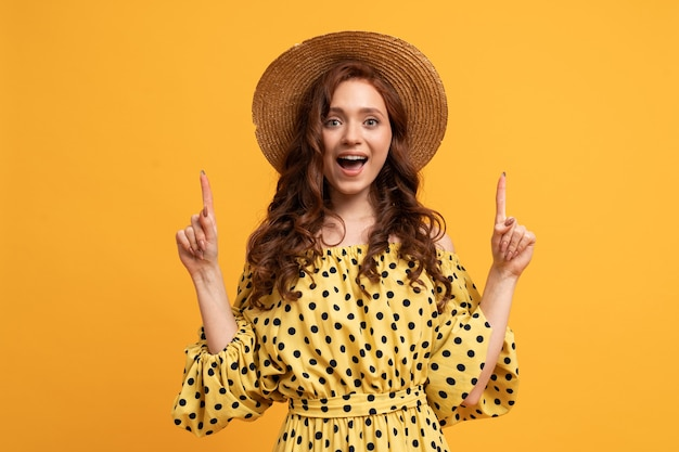 Suprised red-haired woman  posing in yellow dress with sleeves pointing up by fingers on yellow.