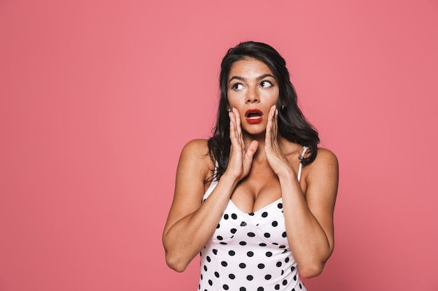 Suprised woman in swimwear posing isolated over pink wall looking aside with mouth opened.