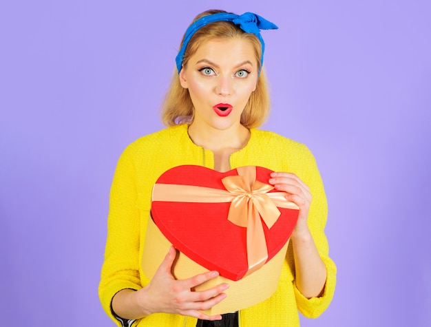 Suprised woman with yellow top and blue bandana holding a red heart shaped box on purple background.