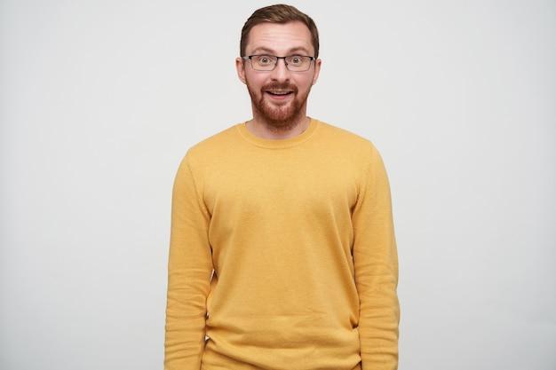 Sorpreso giovane bel ragazzo dai capelli castani con la barba che indossa pullover casual e occhiali mentre in piedi con le mani verso il basso, guardando sorpreso