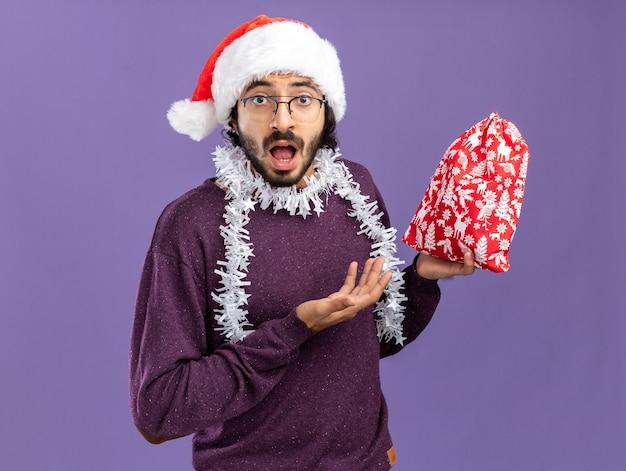 首に花輪と青い背景で隔離のクリスマスバッグを指してクリスマス帽子をかぶって驚いた若いハンサムな男