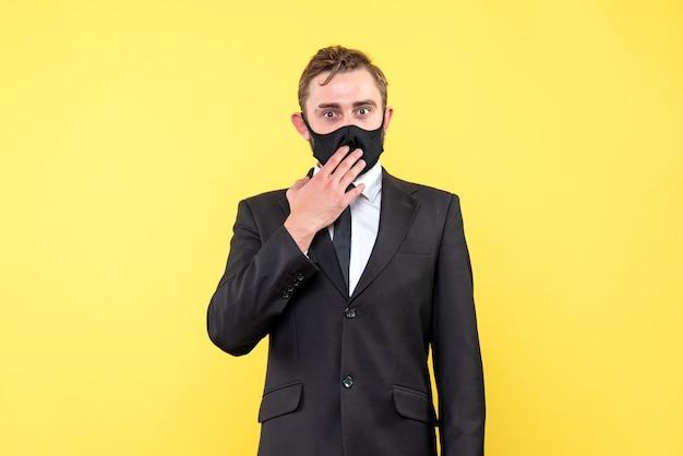 スーツとネクタイが黄色の上に立っている保護マスクで驚いた若い男