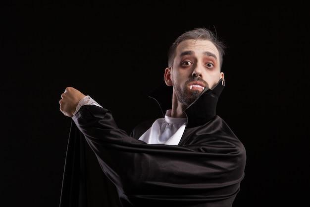 큰 눈을 가진 드라큘라 의상을 입은 놀란 청년. 할로윈 의상에서 악마 모양을 가진 남자입니다.