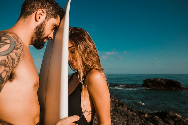 Surf board between young woman and man near sea