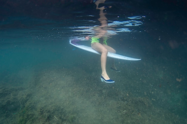 Surf girl sitting on a surfboard with shoes underwater
