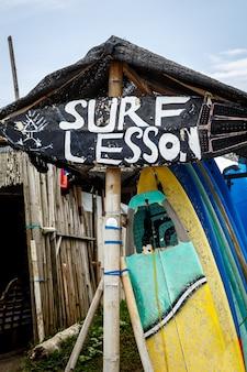 Знак «урок серфинга» на пляже. концепция доски для серфинга.