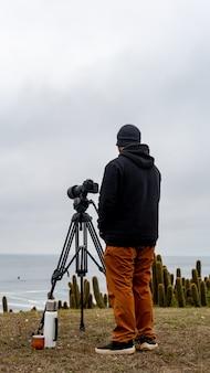カメラ、お湯の魔法瓶、アルゼンチンの仲間と波を待っているサーフフォトグラファー