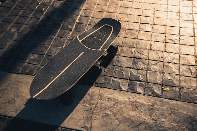 公園の日没でスケートまたはスケートボードをサーフィンします。