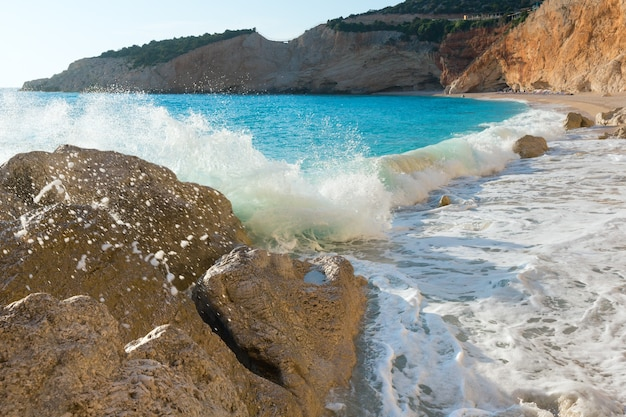 Прибойная волна на красивом летнем белом пляже порто кацики на ионическом море (лефкас, греция)