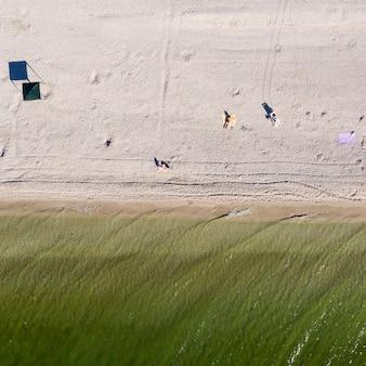 海岸のトップビュー夏の背景に波をサーフィン
