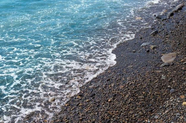 Серфинг с галечного пляжа, летние каникулы на море естественный фон с набегающей волной