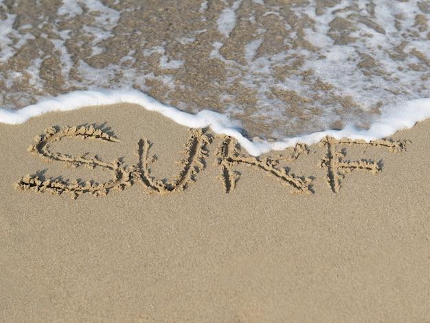 Песчаный пляж с волной и написанное в песке слово surf.