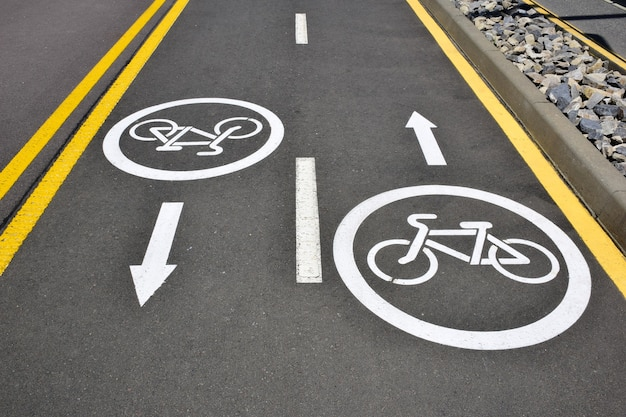 On the surface of the asphalt road, a sign for cyclists in both directions to allow traffic to pass