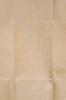 The surface of beige wrapping craft paper with wrinkled lines and shadows.