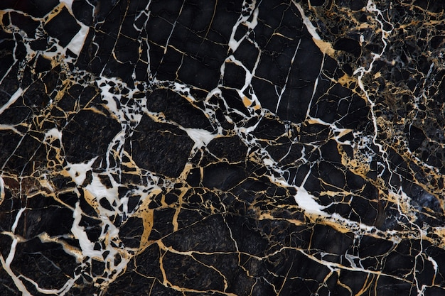 Surface of black marble with yellow and white veins