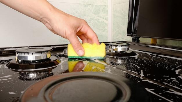 Чистка поверхностей, женщина моет газовую плиту желтой мочалкой и моющим средством.