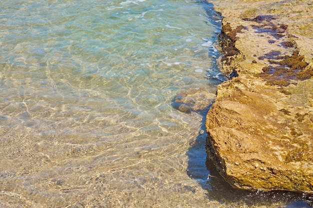 Surface of clear water on tropical sandy beach in crete greece.