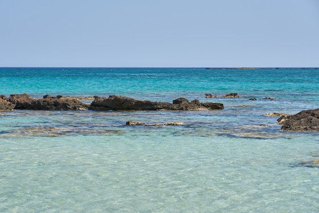 Surface of clear water on tropical sandy beach with stones in crete greece.