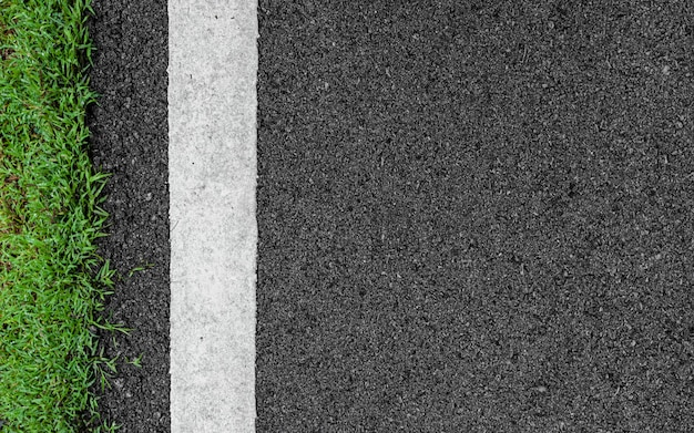 Surface grunge rough asphalt black dark grey road street and green grass texture background