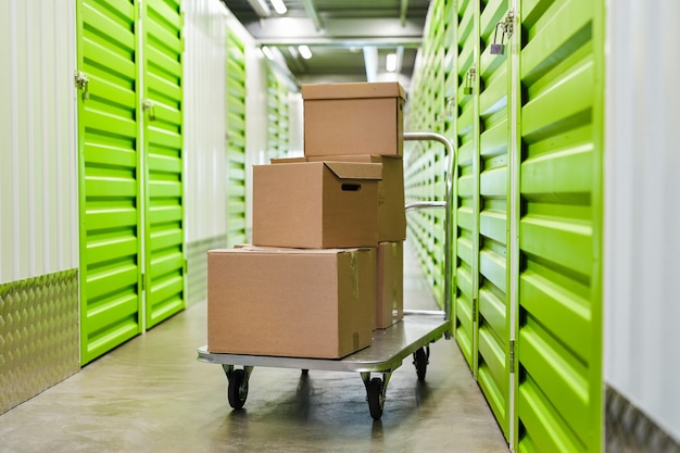 Surface image of cart with cardboard boxes in empty hall of self storage facility, copy space