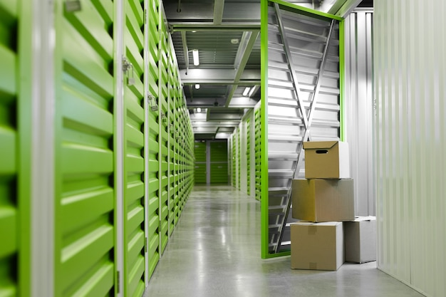 Surface image of green self storage facility with opened unit door and cardboard boxes, copy space