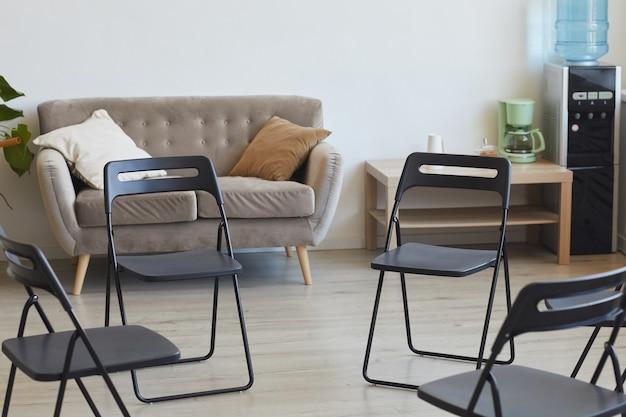 Поверхностное изображение пустых стульев в круге, готовых к сеансу терапии или встрече группы поддержки, место для копирования