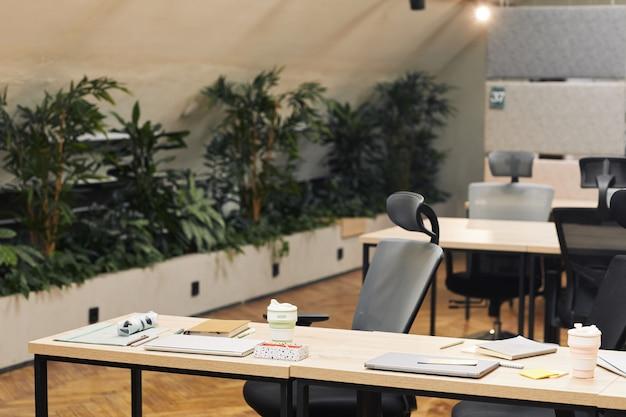 植物で飾られたモダンなオープンスペースオフィスの表面画像、前景に木製のテーブルと人間工学に基づいた椅子、コピースペースのある職場に焦点を当てる
