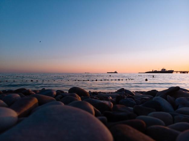 海に沈む夕日に対するビーチの石の表面レベル。ストーンブラックシーショア。波、水しぶき、水面のテクスチャ。絵のように美しいパノラマ風景、コピースペース、グラフィックリソース