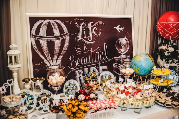 表面-人生は美しいです。結婚式のテーマ-ツアー、旅行、グローブ。お菓子とカラフルなテーブル。キャンディービュッフェでおいしいお菓子。パーティーのデザートテーブル。ケーキ、カップケーキ。