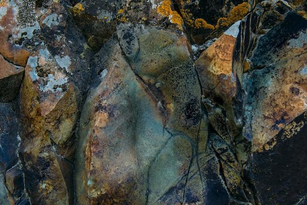 Поверхность старой скалы с трещинами и мхом
