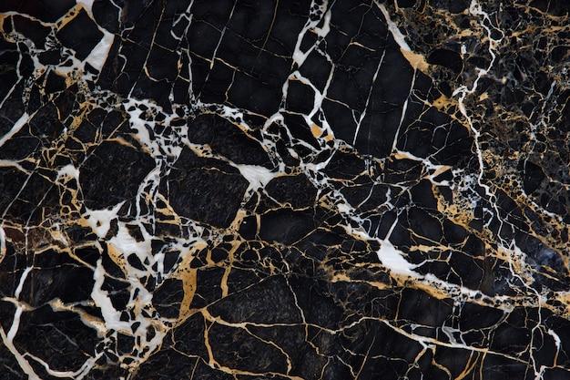 黄色と白の静脈を持つ黒い大理石の表面