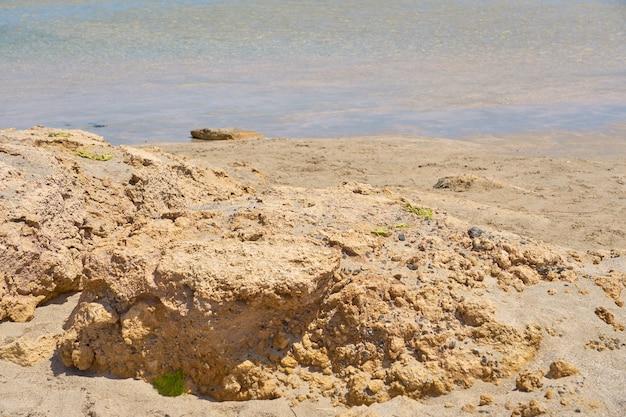 ギリシャのクレタ島の石のある熱帯の砂浜の澄んだ水の表面。