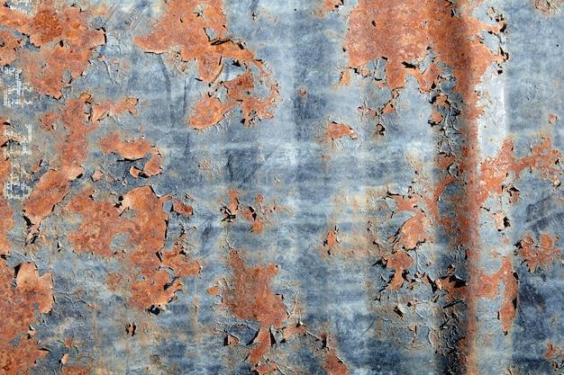 古い剥離塗料で錆びた金属バレルの表面。
