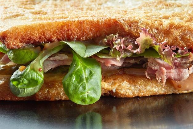 ハム、サラダ、キュウリ、焼きトーストのサンドイッチの表面