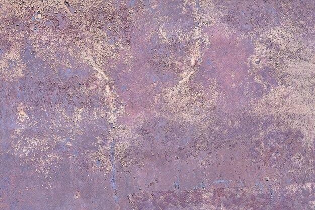 薄片状の薄紫色のペンキが付いているぼろぼろの金属壁の表面。