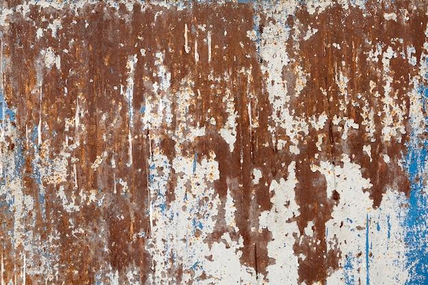 Поверхность стальной стены с отслаивающейся краской и коррозией.