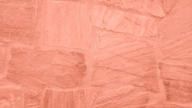 ピンクの色合いの石の壁の表面