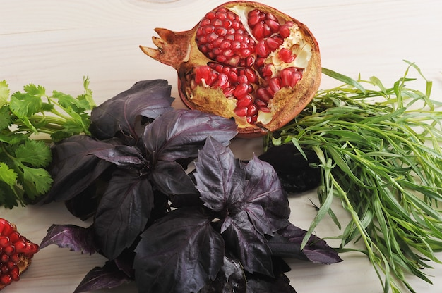 Surface of pomegranate and basil leaves and spinach on white wooden table