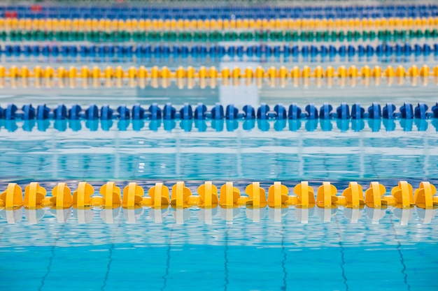 The surface of the pool with blue water and yellow and blue dividers of swimming tracks