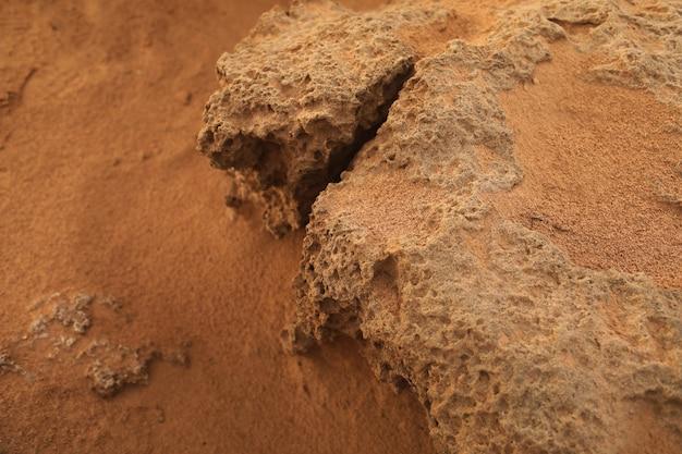 Поверхность песчаного камня. скалистый берег с красным песком средиземного моря. выборочный фокус