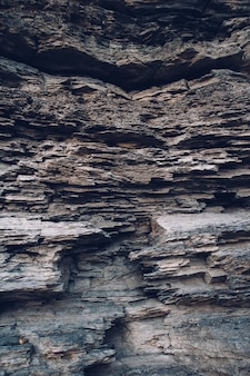 Surface of an stone wall. black stone background. rock texture. rock pile background.