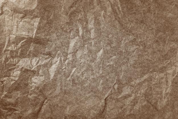 しわくちゃの茶色の古紙のテクスチャーを持つ表面。