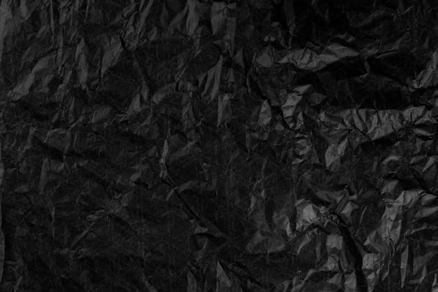 しわくちゃの黒い紙のテクスチャーのある表面。