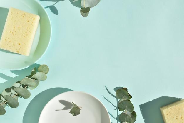 ユーカリの葉の間に皿や皿用のエコスポンジが付いた表面