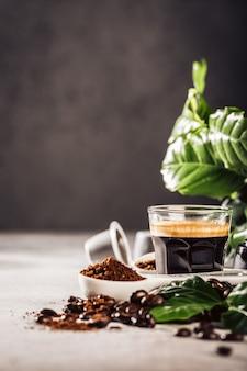 コーヒー、コーヒー豆、葉のガラスカップで表面。コピースペースのある飲料カフェショップのコンセプト