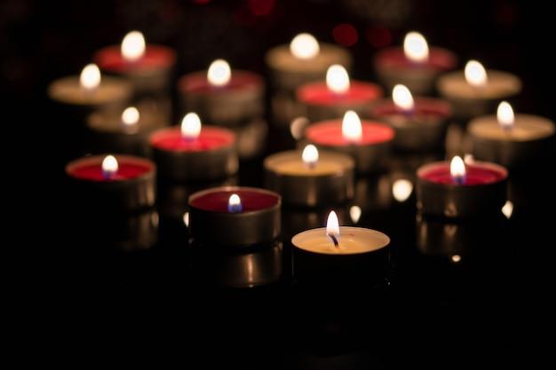Поверхность с чайными свечами светится в темноте. Premium Фотографии